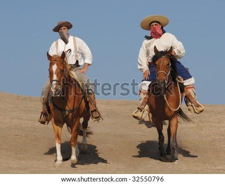 Two banditos riding on horses - stock photo