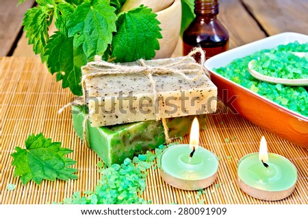 Two bars of homemade soap with twine, bath salt in a bowl, oil in the bottle, nettles in a mortar, two candles on a wooden boards background - stock photo