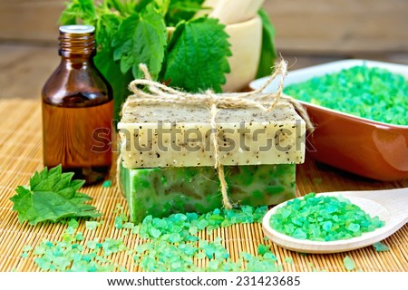Two bars of homemade soap with twine, bath salt, oil bottle, nettle in a mortar on a wooden boards background - stock photo