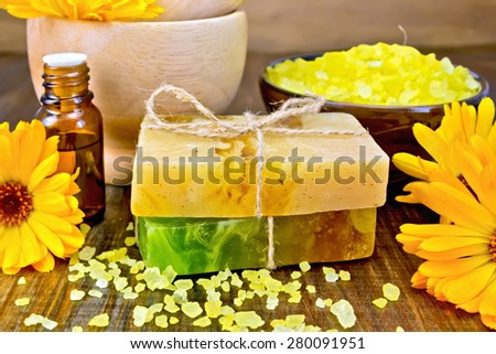Two bars of homemade soap, yellow bath salt, oil in a bottle and marigold flowers on a background of wooden planks - stock photo
