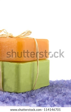 Two bars of natural sandal and olive soap and lavender sea salt on white - stock photo