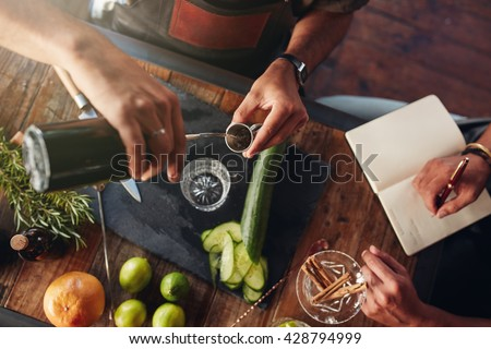 Two bartenders experimenting with creating cocktail drinks. Top view of  man pouring mixture into a jigger to prepare a cocktail and another taking down notes. - stock photo