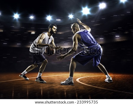 Two basketball players in action in gym in lights - stock photo