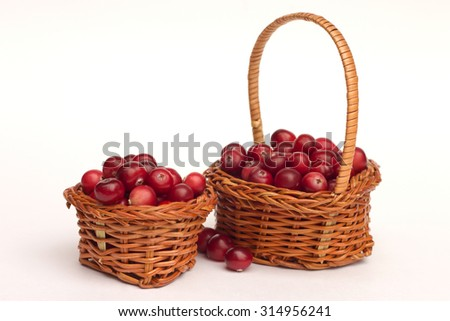 Two baskets full of ripe berries over white background  - stock photo