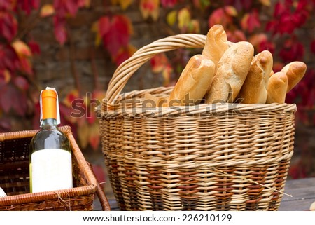 Two baskets with wine and bread in autumn background. - stock photo