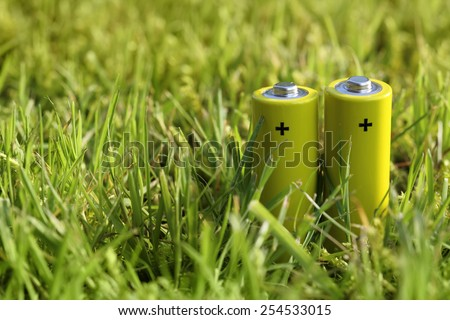 Two batteries on a green grass meadow. Technology and Nature. - stock photo