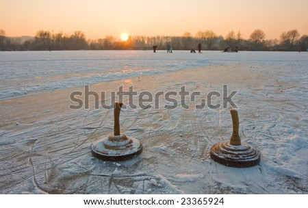 two bavarian curling stones on a frozen lake at sunset - stock photo