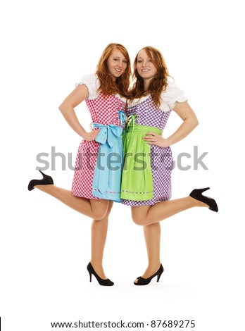 two bavarian dressed girls lifting their feet on white background - stock photo