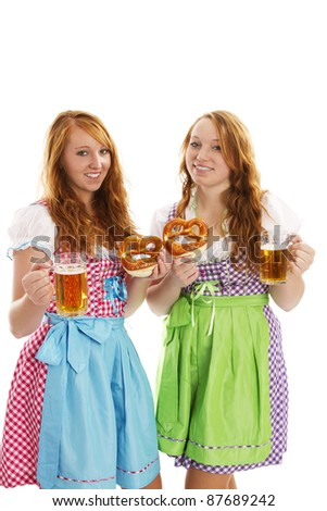 two bavarian dressed girls with pretzels and beer on white background - stock photo