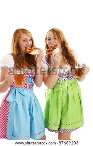 two bavarian dressed women with beer eating pretzels on white background - stock photo