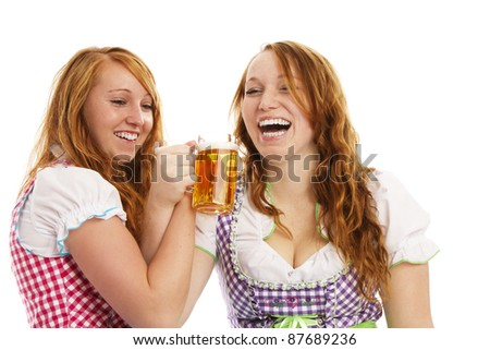 two bavarian girls cheering with beer on white background - stock photo