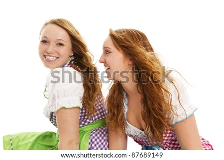 two bavarian girls looking on white background - stock photo