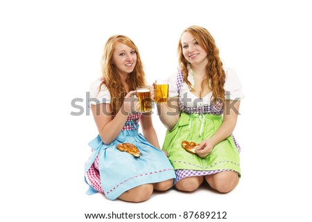 two bavarian girls with pretzels and beer kneeling on floor on white background - stock photo
