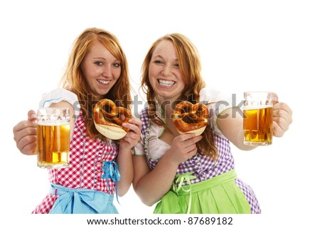 two bavarian girls with pretzels cheering with beer on white background - stock photo