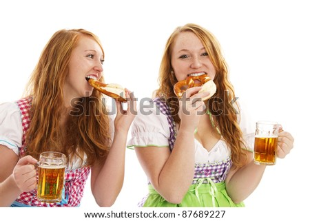 two bavarian women eating pretzels and holding beer on white background - stock photo