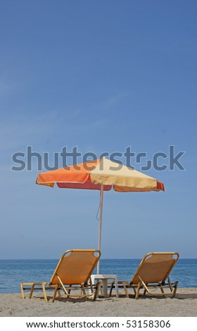 Two beach chairs and a colorful umbrella on the beach