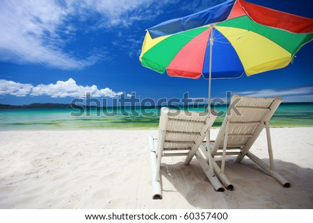 Two beach chairs and colorful umbrella on perfect tropical beach - stock photo
