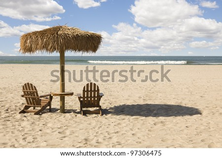Two Beach Chairs and Umbrella on a Beautiful Ocean Front with Copy Space. - stock photo