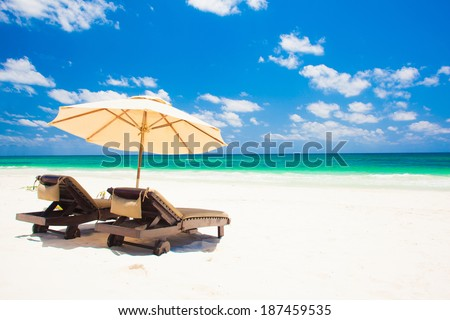 two beach chairs and umbrella on sand beach. Holidays - stock photo