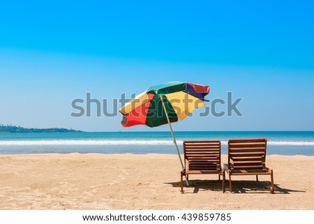 Two beach chairs and umbrella on tropical ocean beach at sunny day - stock photo