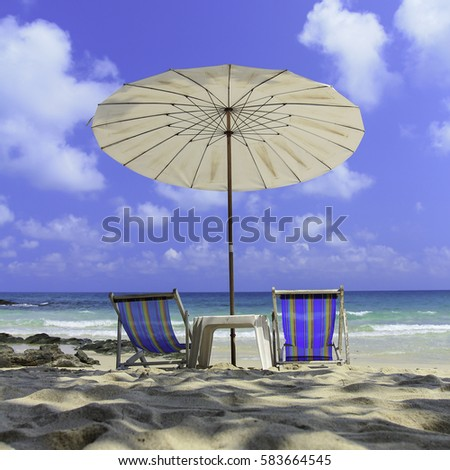 Two beach chairs and umbrellas on the beach sand and blue sky water sea .
