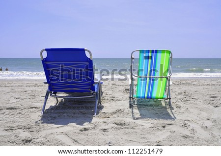 Two beach chairs at the shore - stock photo
