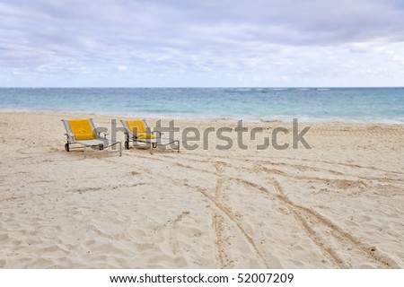 two beach chairs in front of turquoise ocean with shallow depth of field - stock photo