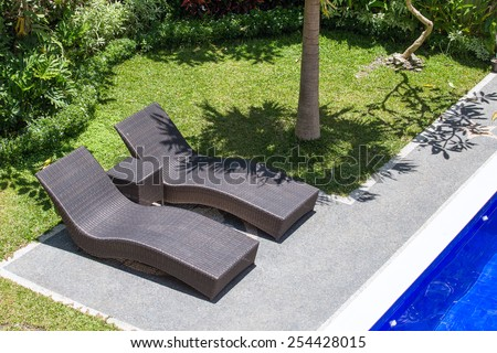 Two beach chairs next to a swimming pool in a tropical garden. Top view. Bali, Indonesia - stock photo