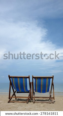 Two beach chairs on tropical beach - stock photo