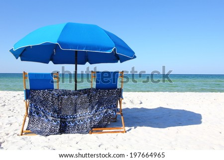 Two beach chairs under a blue umbrella on a white sandy beach - stock photo