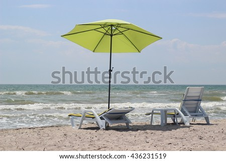 Two beach chairs under a lime umbrella on the white sandy beach at a resort - stock photo