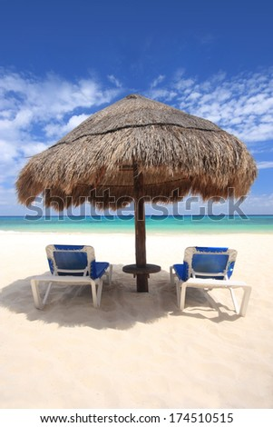Two beach chairs under a palapa thatched sunshade overlooking a tropical beach, Cozumel, Mexico. Copy space available. - stock photo