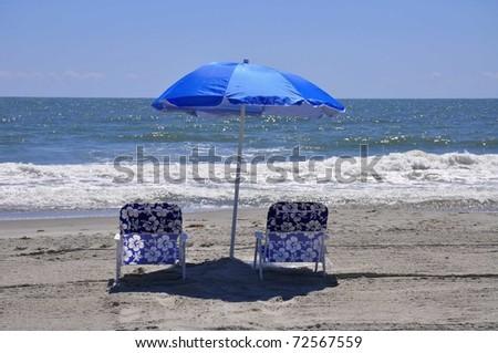 Two beach chairs under a pretty sun umbrella at the shore - stock photo