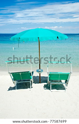 Two beach chairs with green umbrella. - stock photo