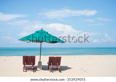 Two beach chairs with sun umbrella on beach
