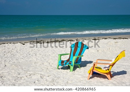 Two Beach Chairs with Towels on the Beach with the ocean in the background - stock photo