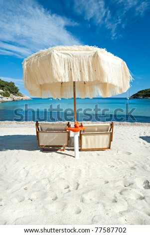 Two beach chairs with umbrella. - stock photo