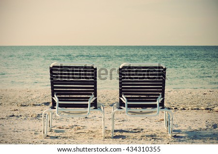 Two Beach Chairsv in front of ocean, retro style    - stock photo