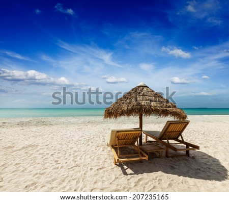 Two beach lounge chairs under tent on beach. Sihanoukville, Cambodia - stock photo