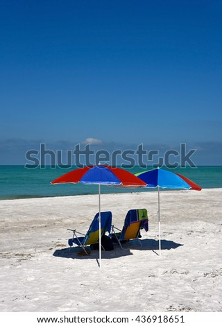 Two Beach Umbrellas and Chairs on the Beach - stock photo