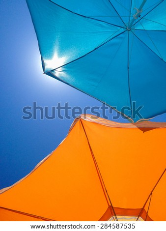Two beach umbrellas on a background of blue sky