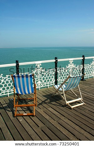 Two beach wooden chairs on dock facing the blue north sea from Pier of Brighton