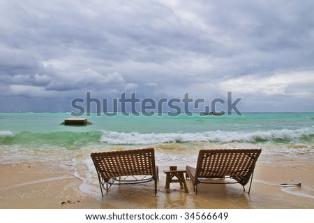 Two Beachbeds on Rainy Beach before Storm - stock photo