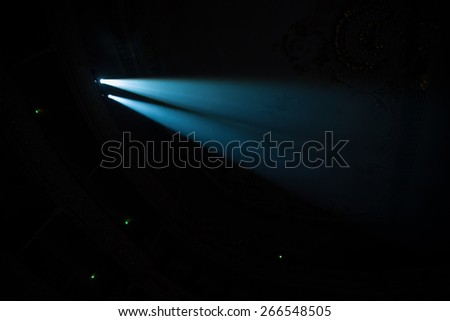 Two beams of searchlights in the dark concert hall.