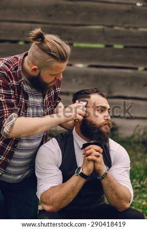 two bearded men shave outdors - stock photo
