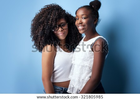 Two beautiful african american girls smiling, looking at camera. Sisters posing on blue background. Studio shot. - stock photo