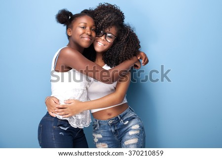 Two beautiful african american girls smiling, looking at camera. Sisters posing on blue background. Studio shot.
