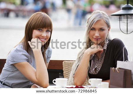 Two beautiful and elegant woman sitting outside in a cafe and looking in camera smiling - stock photo