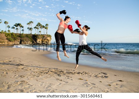 Two beautiful and fit women kick boxing and having fun at beach - stock photo