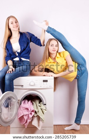 Two beautiful and slim girl sitting on the washing machine